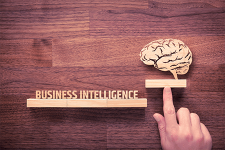 hand pushing carving of brain above blocks spelling business intelligence
